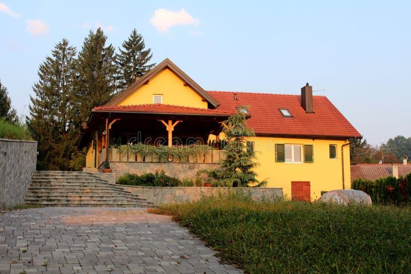 Het vernieuwde gele familiehuis in de voorsteden met grote die portiek in voor en steen betegelt oprijlaan met hoog ongesneden gr royalty-vrije stock foto