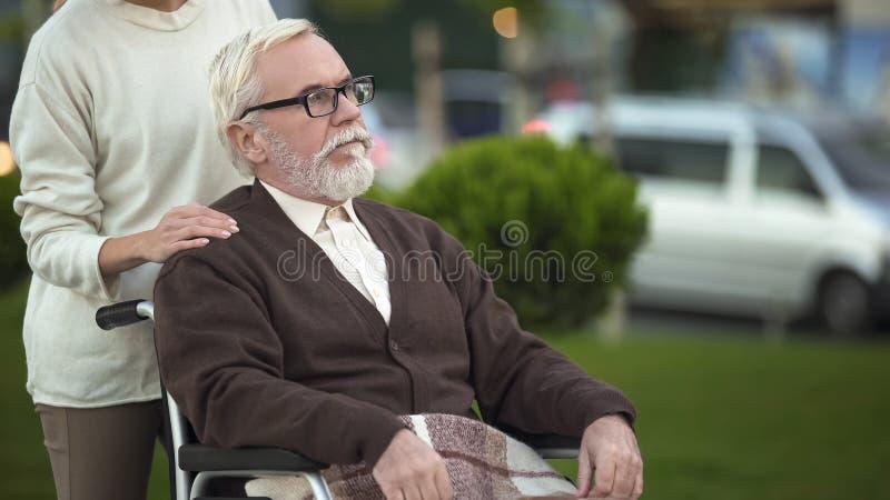 Het verouderen mensenzitting die in rolstoel, kleindochter hem, familiesteun troosten royalty-vrije stock fotografie