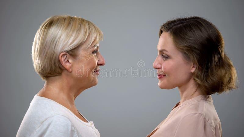 Het verouderen proces, volwassen mum en dochter die elkaar, toekomstige bezinning bekijken royalty-vrije stock afbeelding