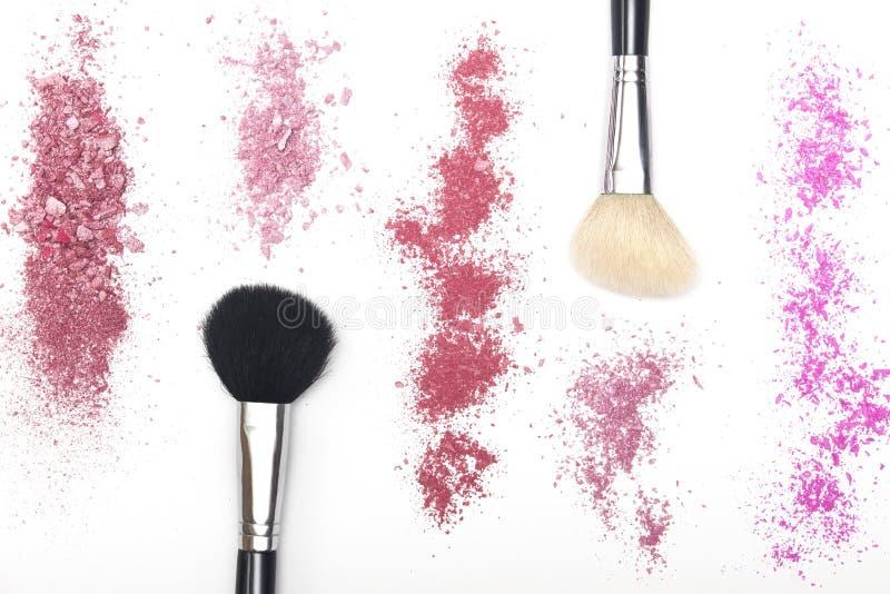 Het verpletterde roze bloost en kosmetische borstels op witte achtergrond stock fotografie