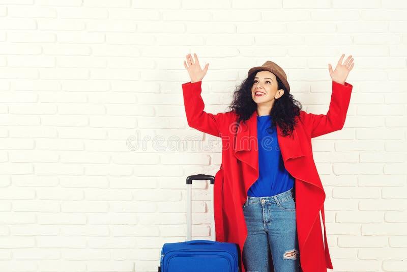Het verrassen van meisje alvorens te reizen De opgewekte jonge Kaukasische vrouw kleedde zich in rode laag en hoed met koffer Vro royalty-vrije stock foto