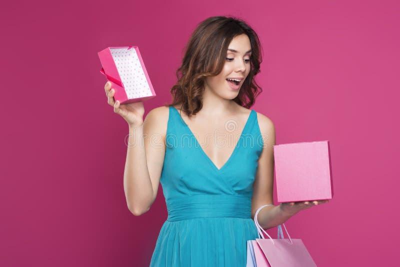 Het verraste brunette onderzoekt open giftdoos stock foto