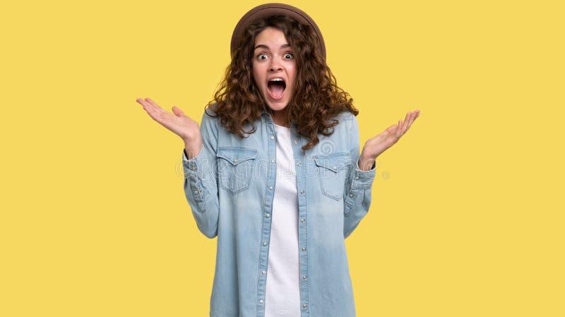 Het verraste jonge brunette met krullend haar heeft uitdrukking op haar gezicht verbaasd, stock afbeelding