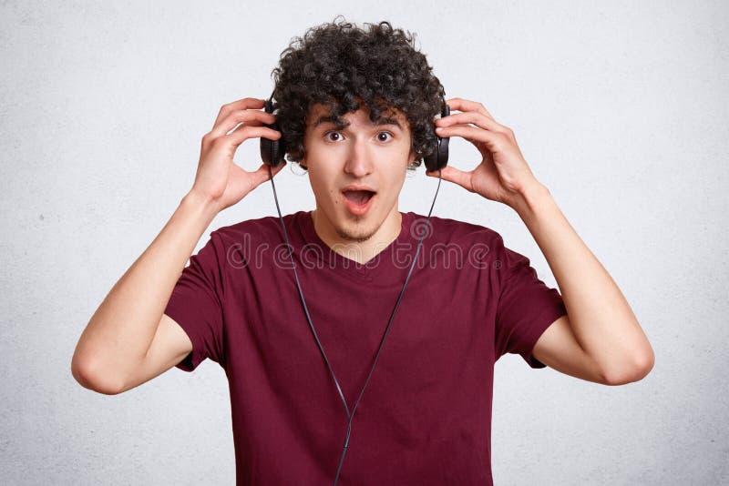 Het verraste kereltje draagt moderne hoofdtelefoons, hoort onverwachte luide muziek of het geluid, houdt kaak gedaald, draagt toe stock foto