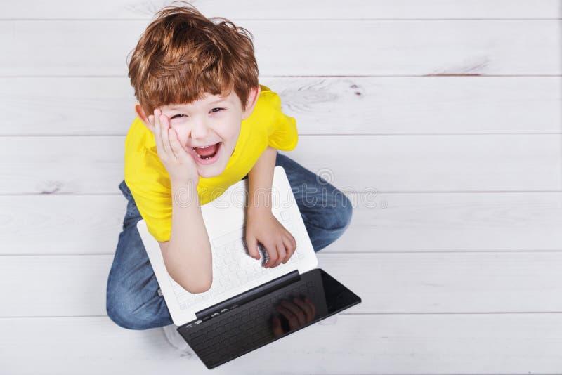 Het verraste kind spelen op notitieboekje bij warm laminaat of