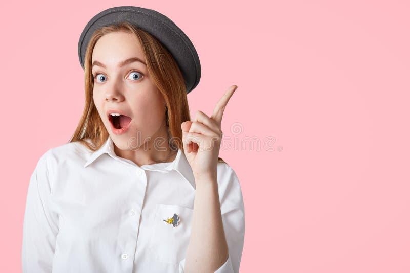 Het verraste mooie Europese wijfje houdt voorvinger opgeheven, draagt elegant overhemd en de hoed, krijgt goed idee om het geïsol stock foto's