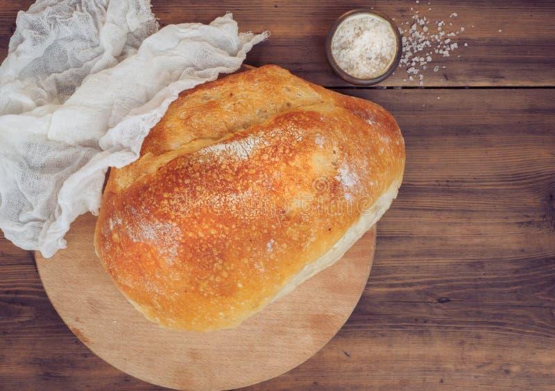 Het verse die brood van brood met een witte doek naast wordt behandeld bestrooit zout op een houten lijst van de oude raad De men stock foto's