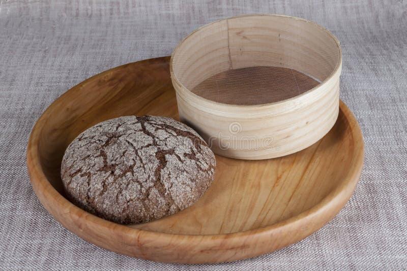 Het verse eigengemaakte brood maakte van durumtarwe, rogge, op een houten dienblad met een zeef voor bloem stock afbeeldingen