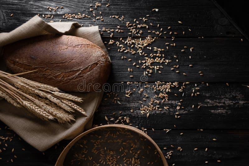 Het verse geurige brood ligt op een houten lijst Zeef met tarwe stock afbeelding