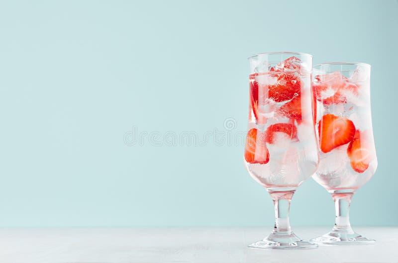 Het verse mineraalwater van de geschiktheidsaardbei met rijpe aardbeiplakken, ijsblokjes en tonicum in elegant glas op witte hout stock foto's