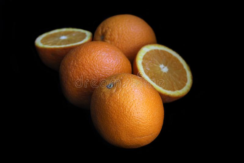 Het verse oranje fruit, sluit omhoog, op zwarte achtergrond stock afbeeldingen