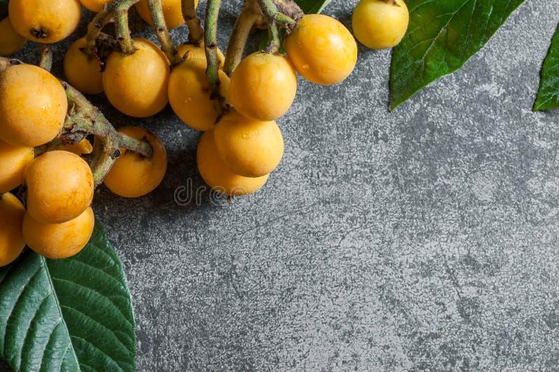 Het verse rijpe fruit van de loquat Japanse mispel met tak en blad op grijze rustieke lijst royalty-vrije stock afbeelding