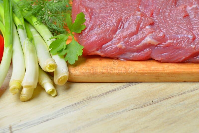 Het verse ruwe stuk van vlees ligt op het keukenbord stock foto's