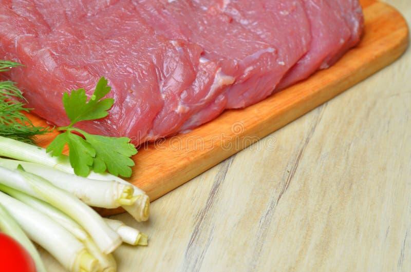 Het verse ruwe stuk van vlees ligt op het keukenbord stock foto