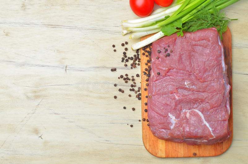 Het verse ruwe stuk van vlees ligt op het keukenbord stock afbeeldingen