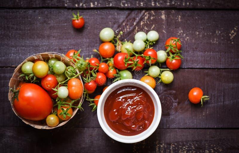 Het verse tomaten organische oogsten op mand en ketchup in koptomatensaus op houten donkere achtergrond stock foto's