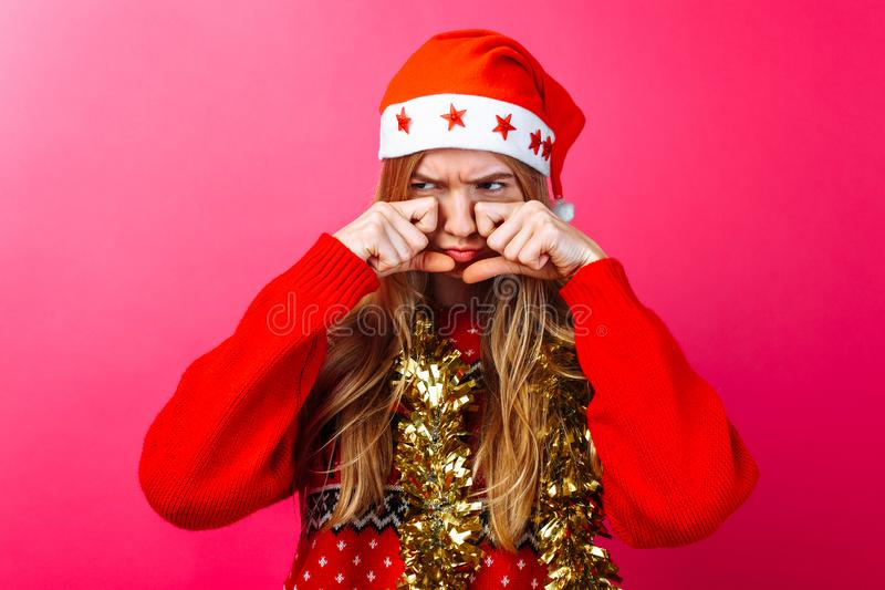 Het verstoorde meisje in de hoed van de Kerstman en met klatergoud op haar hals, wrijft haar ogen en wil met wrok op een rode ach royalty-vrije stock foto's