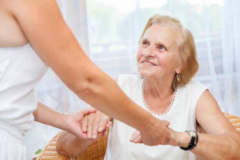 Het verstrekken van zorg voor bejaarden stock foto's
