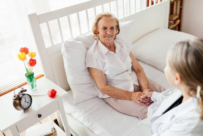 Het verstrekken van zorg voor bejaarden Arts die bejaarde patiënt thuis bezoeken royalty-vrije stock foto's