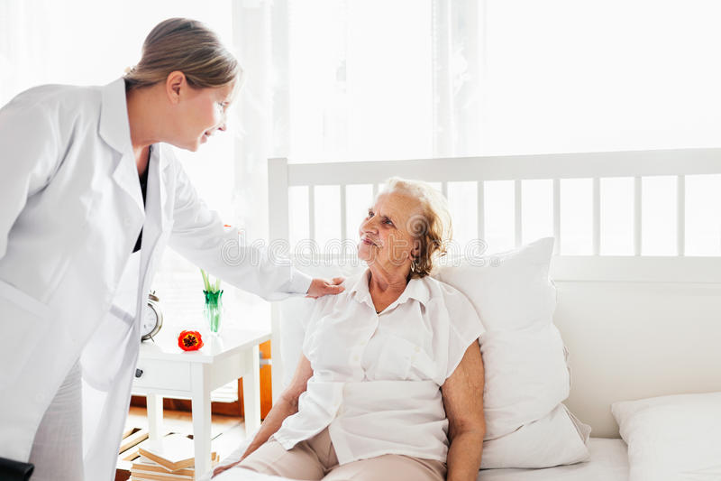 Het verstrekken van zorg voor bejaarden Arts die bejaarde patiënt thuis bezoeken stock foto's
