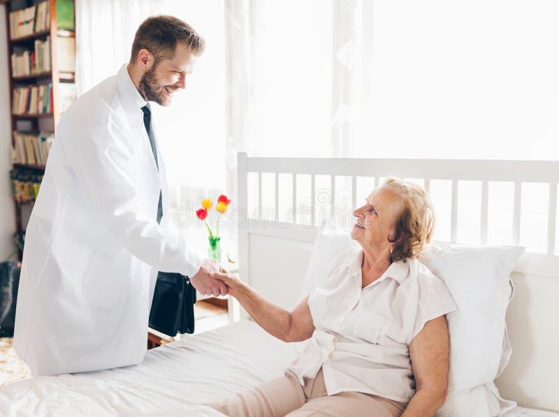 Het verstrekken van zorg voor bejaarden Arts die bejaarde patiënt thuis bezoeken stock foto