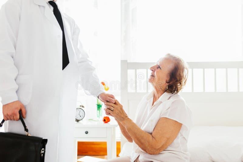 Het verstrekken van zorg voor bejaarden Arts die bejaarde patiënt thuis bezoeken royalty-vrije stock afbeeldingen