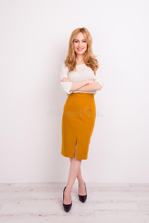 Het verticale businesslady portret van gemiddelde lengte van het mooie glimlachen stock afbeelding