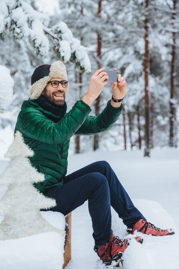 Het verticale mannelijke portret van het prettige kijken maakt foto met smartphone, maakt schoten van mooie de winterlandschappen stock foto's