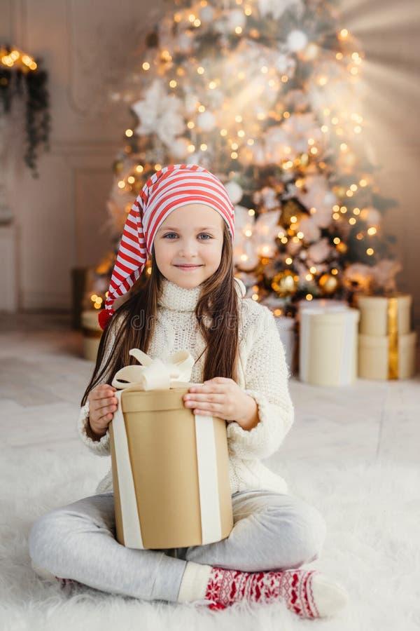 Het verticale portret van mooi prettig kijkend klein kind draagt gebreide sweater en de sokken, zit gekruiste benen met heden, he stock afbeeldingen
