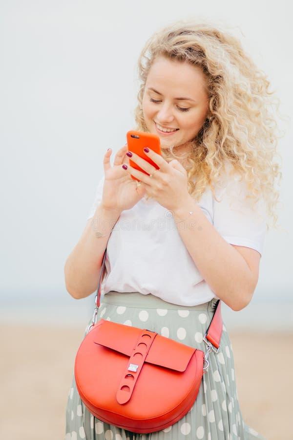 Het verticale portret van mooie jonge vrouw heeft licht krullend haar, houdt moderne cellulair, gelukkig om foto van minnaar in s stock foto