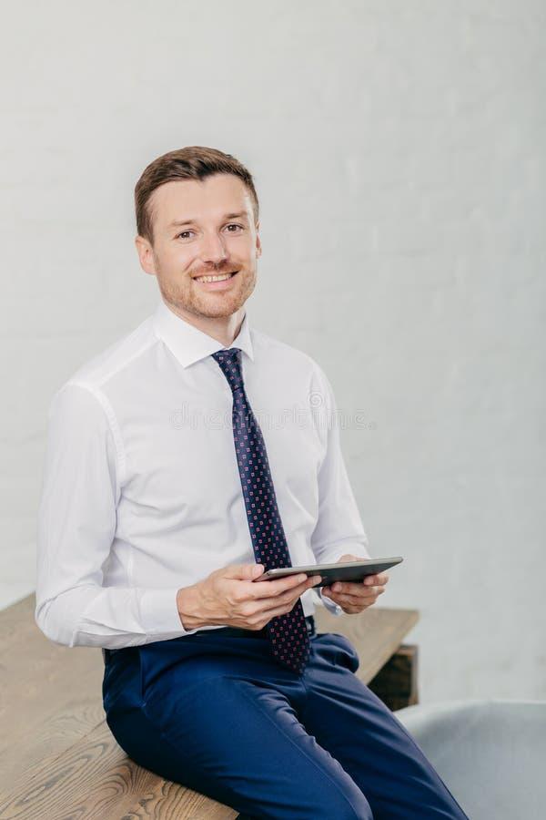 Het verticale schot van gelukkige zakenman in formele kleding controleert e-mail en leest bericht op moderne tabletcomputer, zit  royalty-vrije stock afbeelding