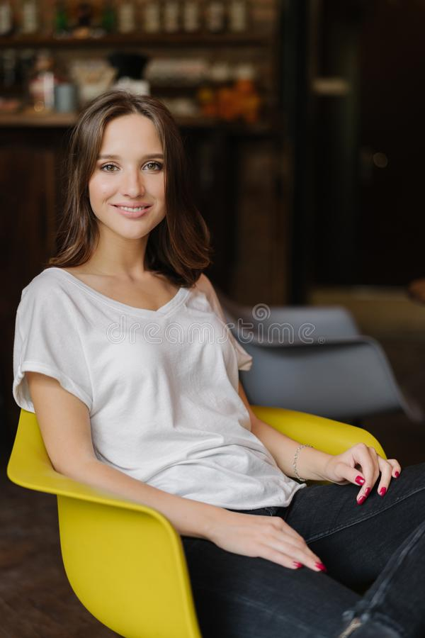 Het verticale schot van glimlachende vrouw heeft donker haar, toothy glimlach, gekleed in witte t-shirt, zit in gele leunstoel, h stock afbeelding