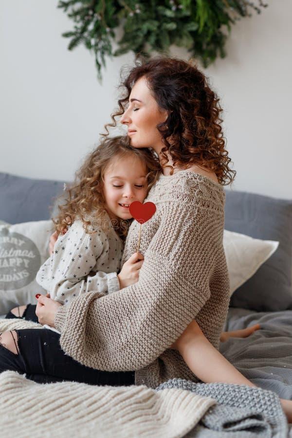 Het verticale schot van hartelijke jonge moeder en haar daugher omhelzen elkaar en de uitdrukkelijke liefde, zit op comfortabel b royalty-vrije stock foto's