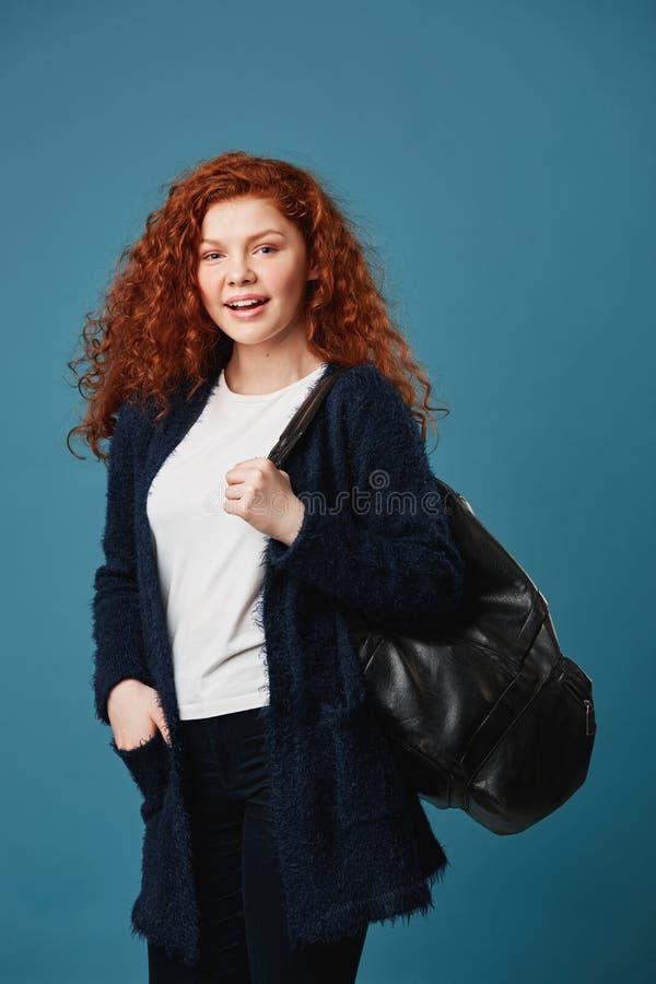 Het verticale schot van knap jong rood haired studentenmeisje met golvende kapselholding dient zak in, brightfully glimlachend stock afbeelding