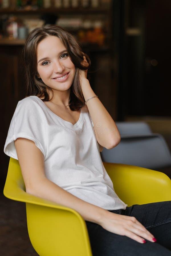 Het verticale schot van mooi meisje gekleed in witte t-shirt en de jeans, hebben gelukkig om camera te bekijken, zitten bij gele  royalty-vrije stock afbeeldingen