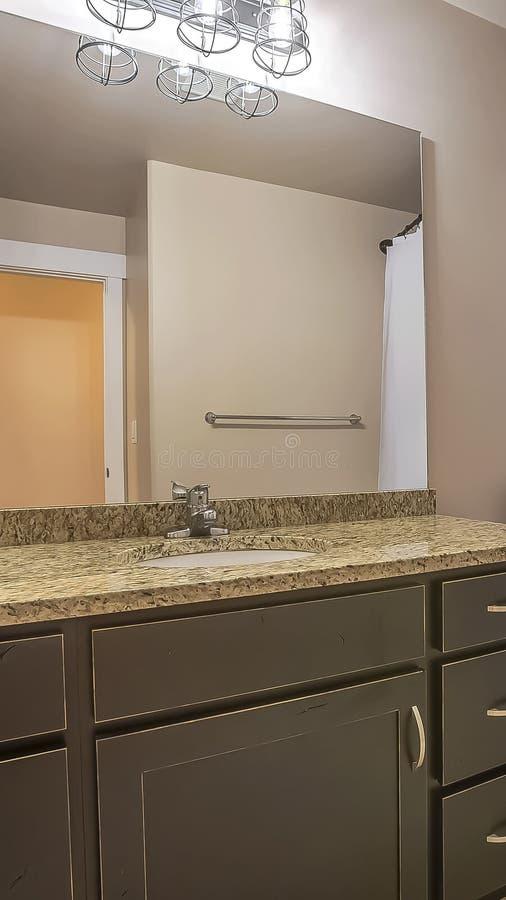 Het verticale toilet en de handdoek van de Ijdelheidseenheid haken tegen de witte muur van een goed aangestoken badkamers vast stock fotografie