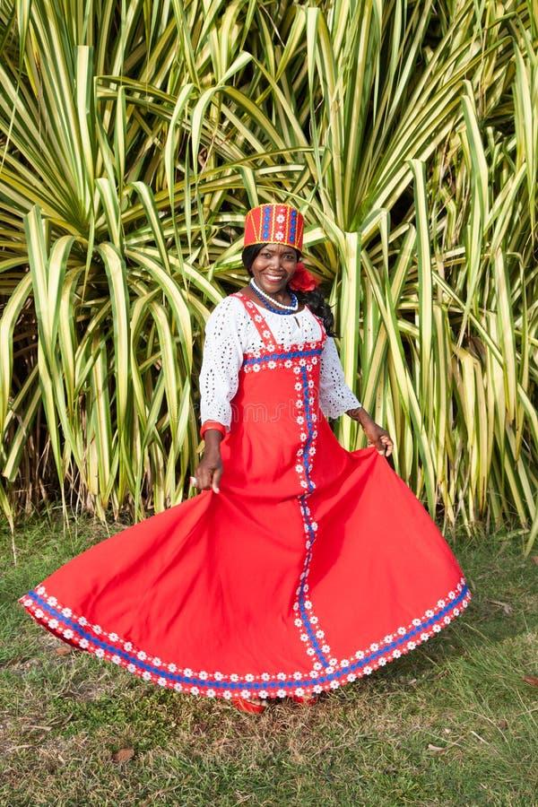 Het verticale volledige lichaam van een blije Afrikaanse Amerikaanse vrouw in een heldere kleurrijke nationale Russische kleding royalty-vrije stock fotografie