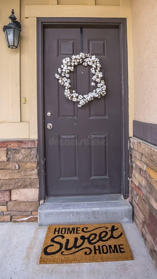 Het verticale Witte kroon hangen op grijze voordeur van huis met een deurmat door de drempel royalty-vrije stock afbeelding