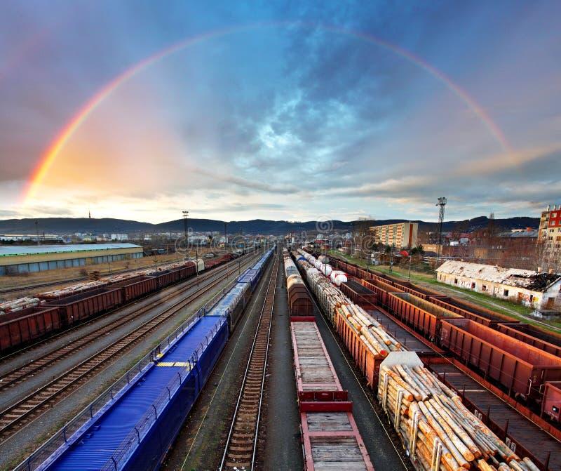 Het vervoer van de treinvracht met regenboog - Ladingsdoorgang stock foto