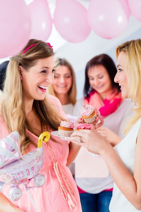 Het verwachten van moeder die cupcake op de partij van de babydouche eten royalty-vrije stock fotografie