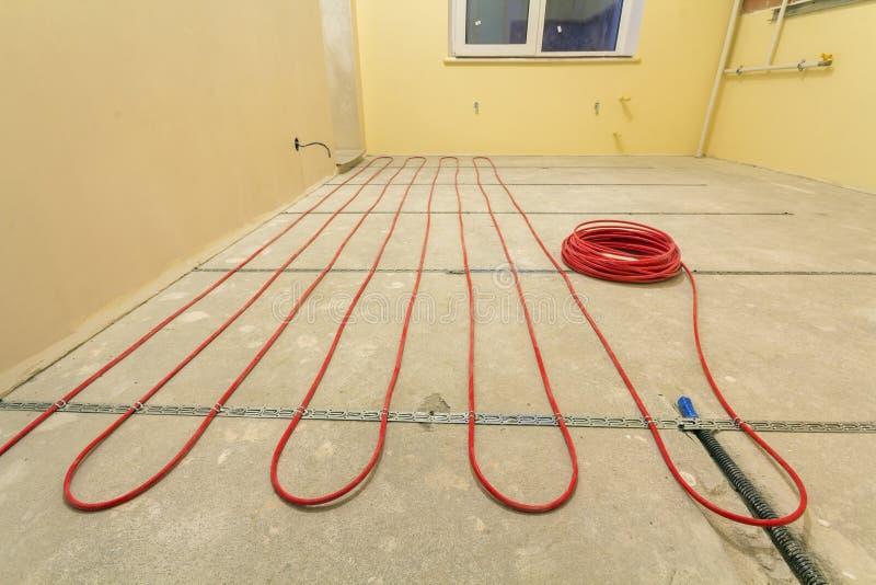 Het verwarmen van de rode elektroinstallatie van de kabeldraad op cementvloer in kleine nieuwe onvolledige ruimte met gepleisterd stock foto