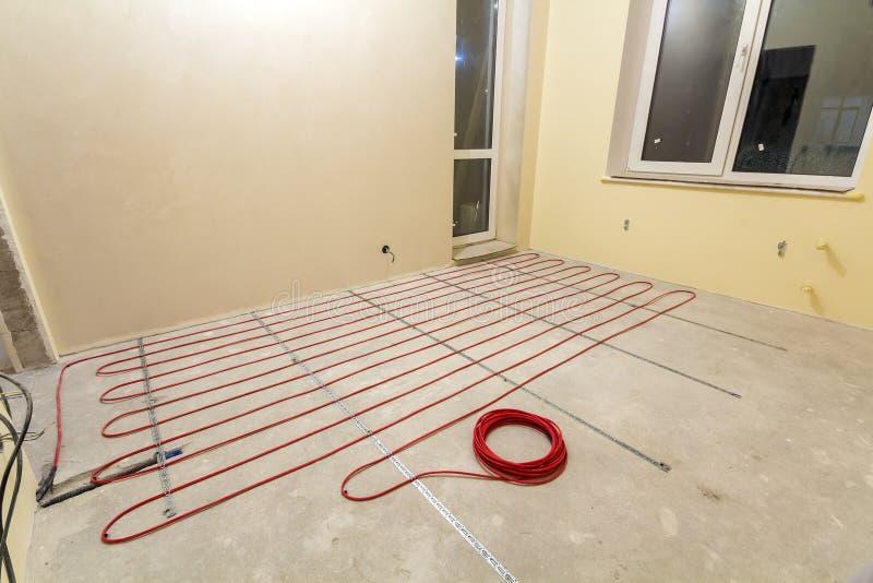 Het verwarmen van de rode elektroinstallatie van de kabeldraad op cementvloer in kleine nieuwe onvolledige ruimte met gepleisterd royalty-vrije stock foto's