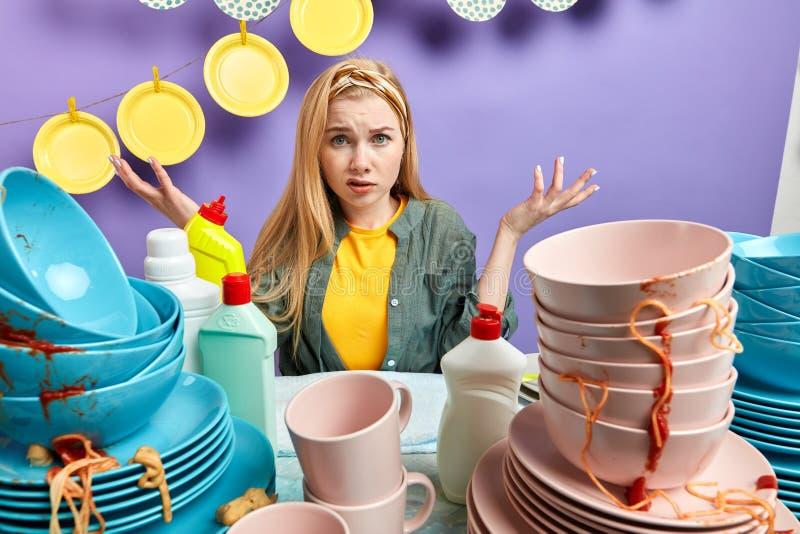 Het in verwarring gebrachte blondemeisje in modieuze toevallig kleedt zitting achter de slordige keuken royalty-vrije stock foto's