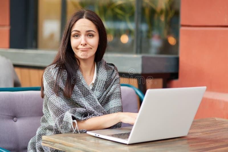 Het in verwarring gebrachte vermoeide wijfje freelancer maakt online die onderzoek van informatie, in warme sprei wordt verpakt,  stock foto's