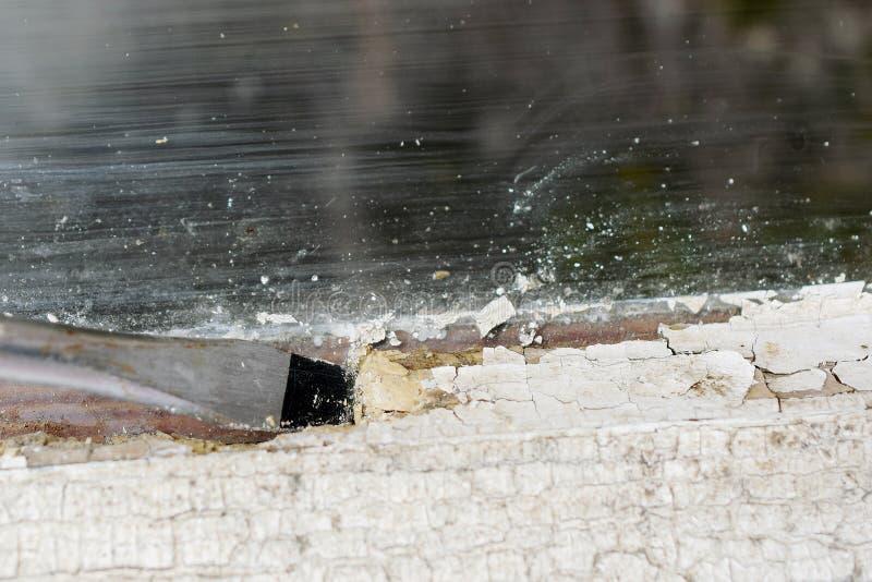 Het verwijderen van verglazingsstopverf uit oude vensterclose-up royalty-vrije stock afbeelding
