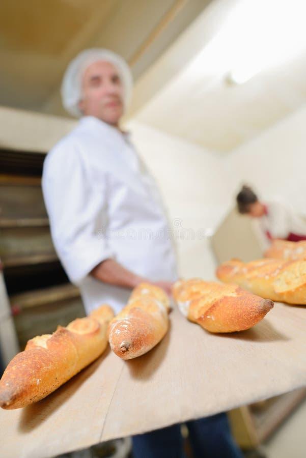 Het verwijderen van verse broodstokken uit oven royalty-vrije stock foto's