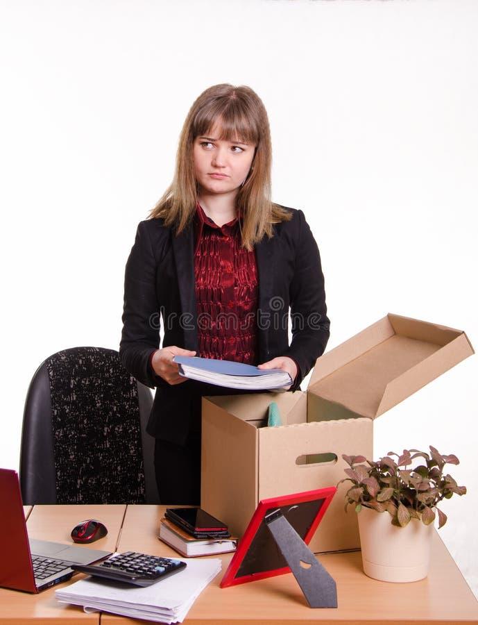 Het verworpen meisje verzamelt zijn bezittingen in een doos stock fotografie