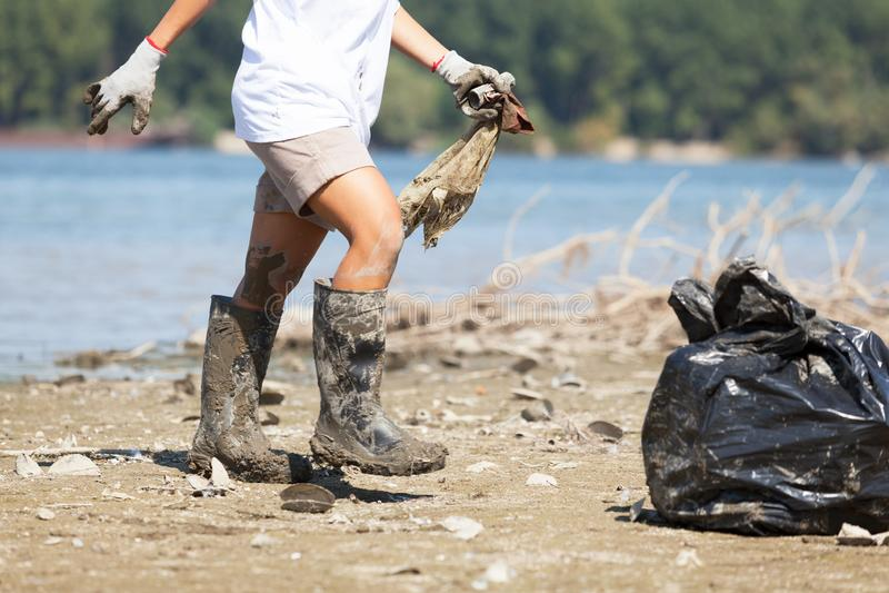 Het verzamelen van plastic afval bij rivier of meerkust stock afbeeldingen