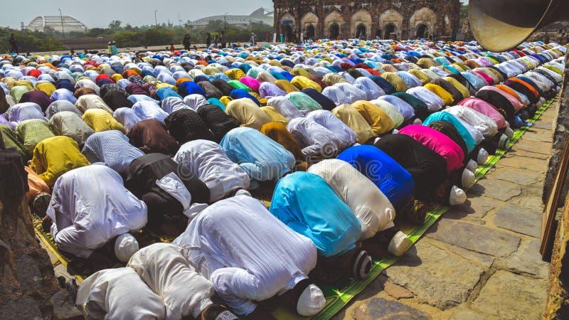 Het verzamelen zich van Moslimmensen en kinderen die neer en Namaz-gebeden ter gelegenheid van Eid 'al-Fitr buigen aanbieden royalty-vrije stock afbeeldingen