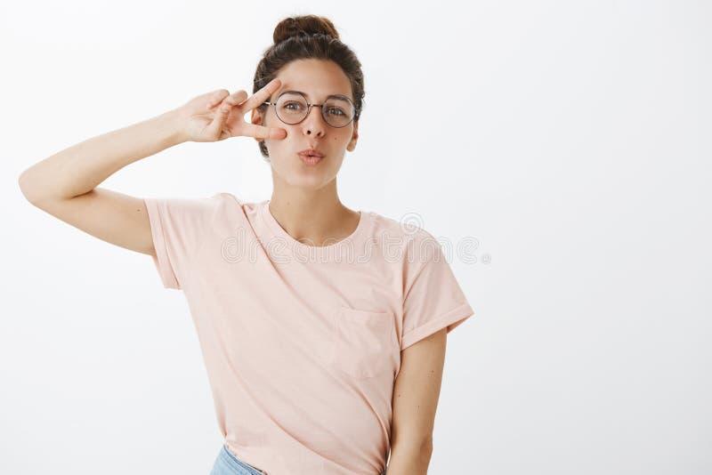 Het verzenden van positieve vibes Blije zekere en charismatische modieuze vrouw in t-shirt en ronde glazen die vredesteken tonen stock fotografie